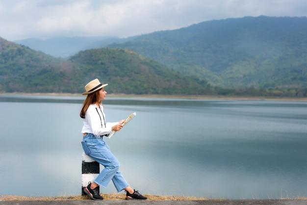 O viajante asiático bonito novo da mulher com câmara digital e mapa nas mãos que olham e felizes ver a vista da paisagem senta-se em um lago com mountain view bonito em tailândia. viagem de mulher solo