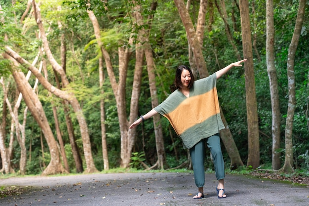 O viajante asiático da menina da felicidade aprecia no parque nacional com fundo verde das árvores.