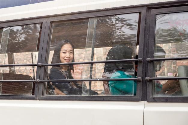 O viajante asiático da mulher que sitiing em uma mão de ondulação do ônibus disparou através da janela de vidro.