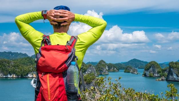 O viajante com mochila aproveita a vista de roks na baía de kabui perto de waigeo. papuásia ocidental, raja ampat, indonésia
