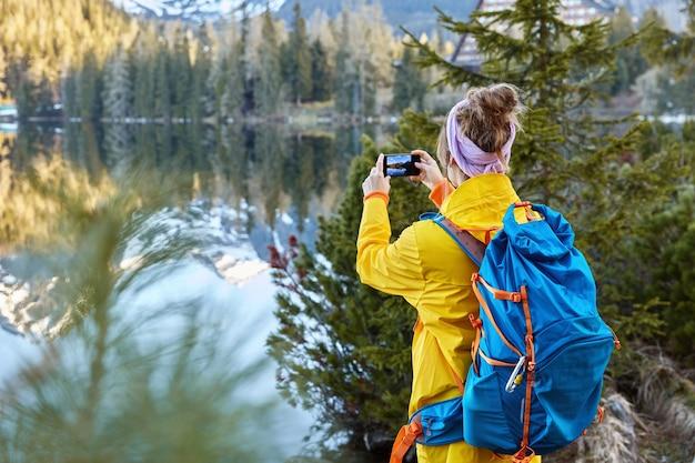 O viajante da liberdade tira fotos da vista panorâmica da natureza, tenta capturar o belo lago com montanhas e floresta, fica para trás