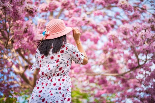 O viajante de mulher em pé de volta com fundos de flores de trombeta-de-rosa