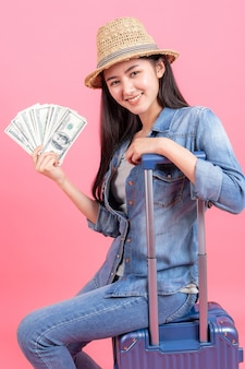 O viajante de mulher usando chapéu traw está segurando o passaporte com notas e sentado na mala.