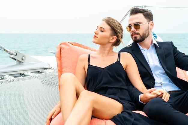 O viajante de relaxamento luxuoso dos pares no vestido e na série agradáveis senta-se no saco de feijão na parte do iate do cruzeiro.