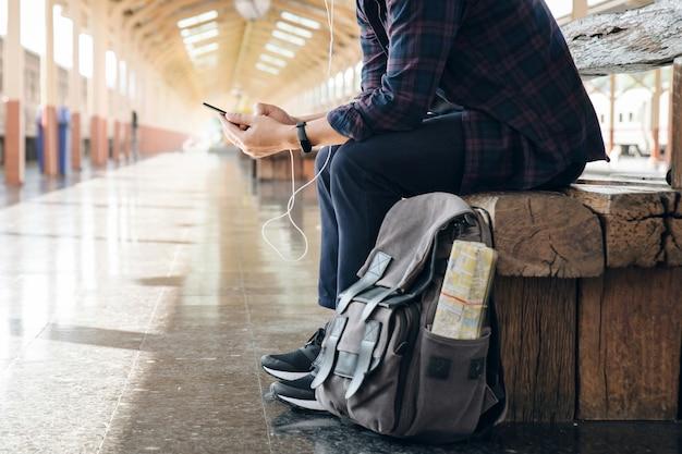 O viajante do homem novo que senta-se com uso de telefone celular escolhe onde viajar e ensaca o trem de espera na estação de trem. mochileiro na estação de trem e procurando no telefone celular o plano para viajar.