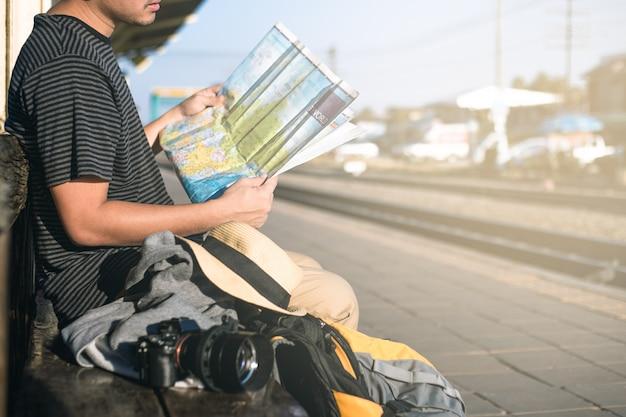O viajante está esperando o trem para ter uma bolsa de câmera, mapa e chapéu.