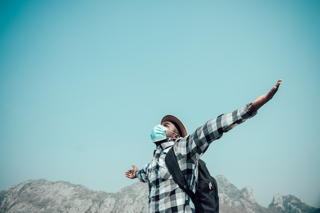 O viajante está usando máscara protetora e viajando pela montanha