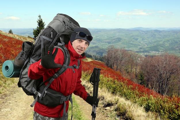 O viajante feliz equipado com uma jaqueta vermelha na encosta levantada na mão de saudação
