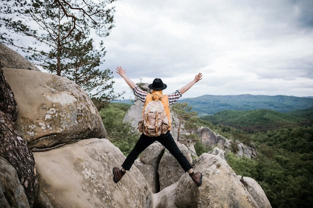 O viajante fica no topo de um penhasco sozinho nas montanhas com uma mochila Foto Premium