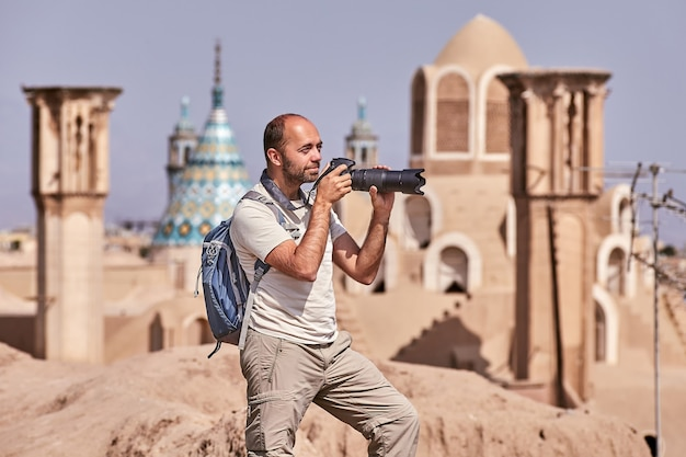 O viajante individual tira fotos na cidade velha durante uma viagem individual independente, kashan, irã.