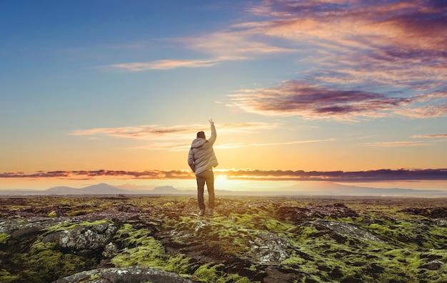O viajante levanta o braço para o céu ao nascer do sol