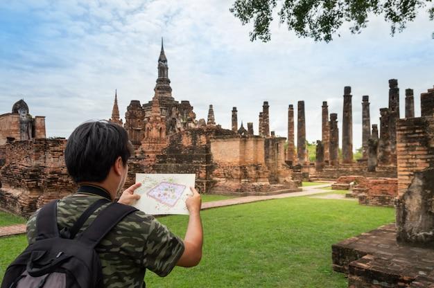 O viajante masculino asiático está vendo o mapa do parque histórico de sukhothai. na tailândia