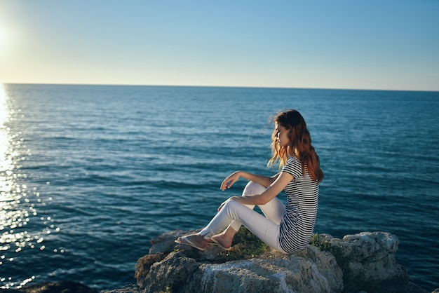 O viajante se senta na praia perto do mar nas montanhas e o pôr do sol