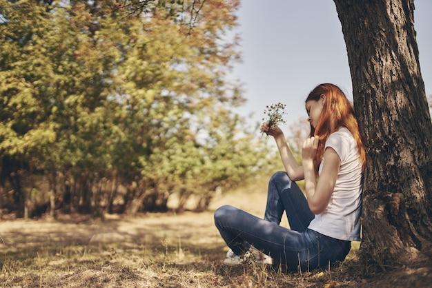 O viajante senta-se perto de uma árvore ao ar livre na floresta, de jeans e camiseta.