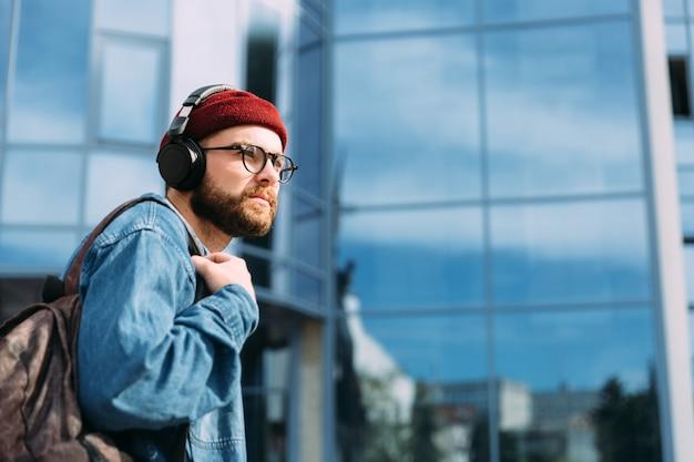 O viajante sério moderno jovem hippie em fones de ouvido caminha na cidade. esquema de cores azul. cena urbana com espaço de cópia.