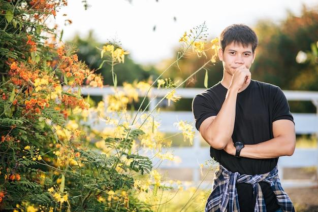 O viajante veste uma camisa preta e fica em um jardim de flores.