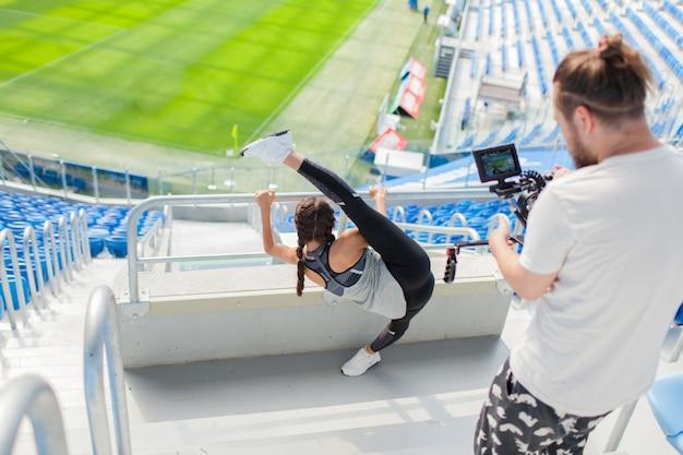 O videomaker dispara a menina em uma câmera profissional.