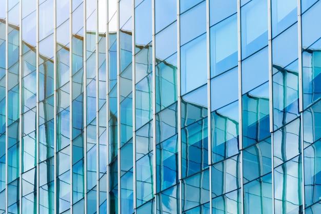 O vidro azul da construção moderna surge o fundo da arquitetura.