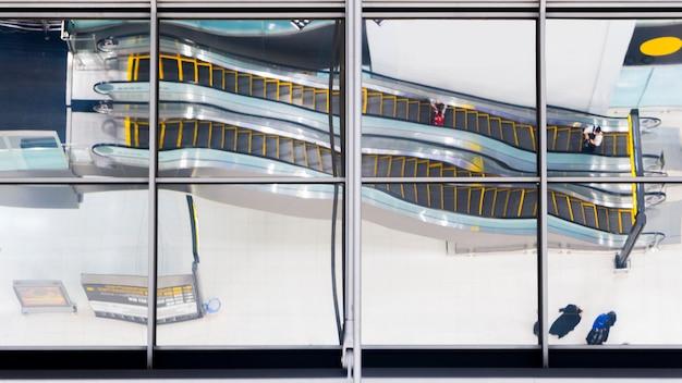 O vidro da reflexão de povos da vista superior anda e senta a escada rolante da escada no aeroporto.