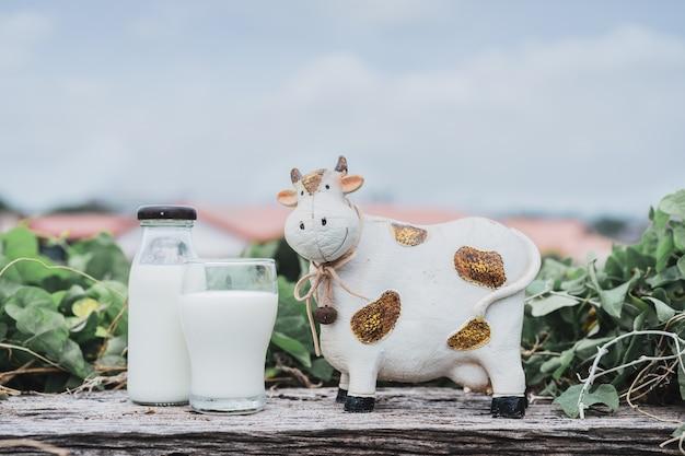O vidro de garrafa do leite com a boneca da vaca de leite da resina do borrão no fundo da natureza e do céu azul.