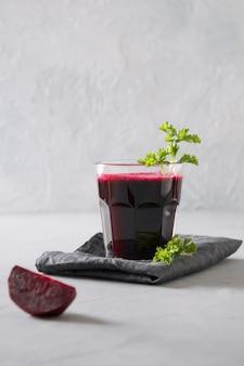 O vidro do suco de beterrabas fresco decora a salsa no cinza. orientação vertical.