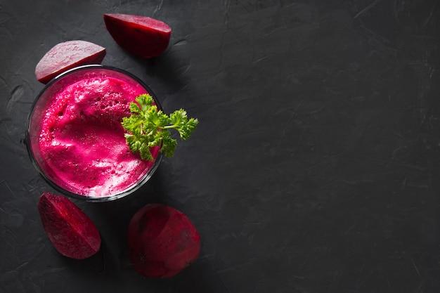 O vidro do suco de beterrabas fresco decora a salsa no preto.