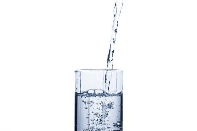 O vidro está enchendo com um fluxo de água limpa e refrescante.