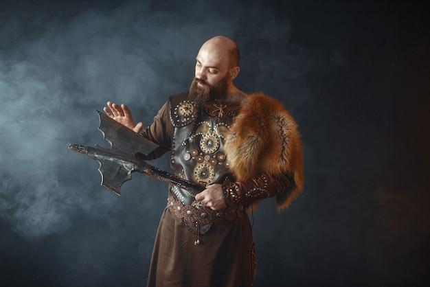 O viking barbudo vestido com roupas nórdicas tradicionais toca a lâmina do machado