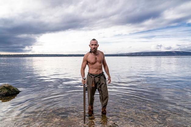 O viking com uma espada nas mãos está contra o fundo do rio e do céu