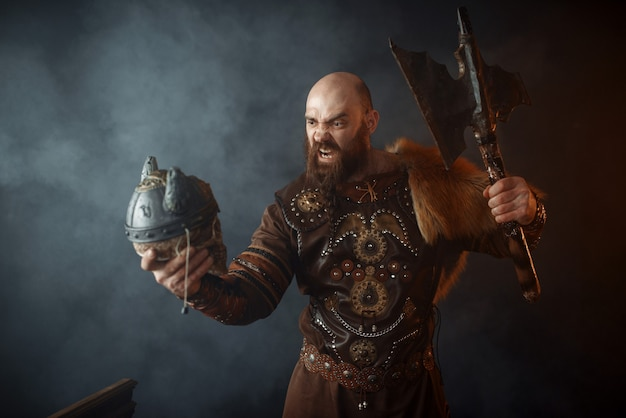 O viking furioso, vestido com roupas nórdicas tradicionais, segura o crânio do inimigo no capacete e no machado