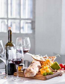 O vinho tinto, baguete e queijo no espaço de madeira