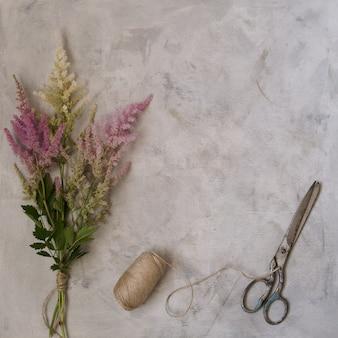 O vintage bonito zomba acima com flores, astilba colorido, tesouras velhas e linhas de linho em um fundo cinzento. vista de cima, copie o espaço