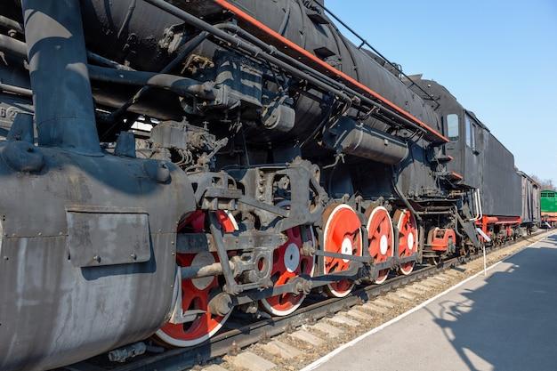 O vintage vermelho do trem velho roda na estrada de ferro.