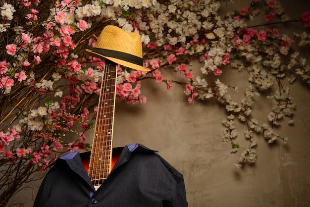 O violão está vestido com uma camisa azul do homem e um chapéu com uma escala perto de uma parede de flores