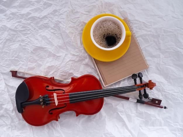 O violino de madeira colocado ao lado da xícara de café de cerâmica amarela