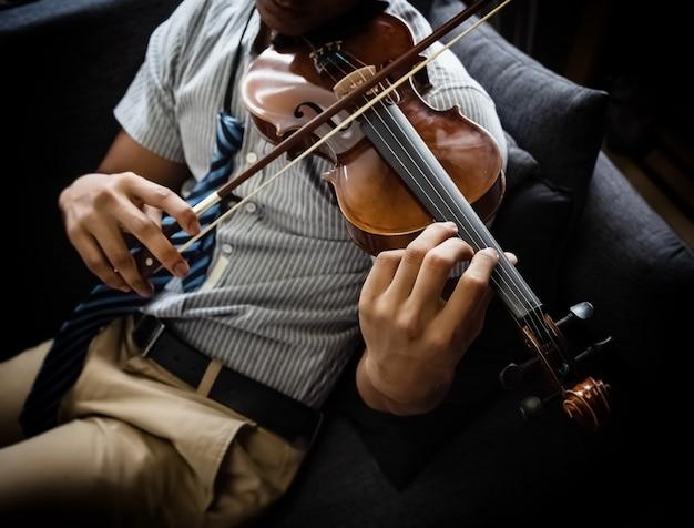 O violino de madeira estava segurando por mãos humanas e tocando, vintage e arte, estilo clássico, luz embaçada ao redor