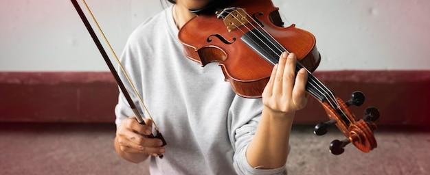 O violino estava sendo segurado pela mão de uma mulher, o dedo pressionando a corda e o arco preparando-se para tocar