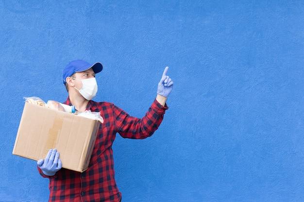 O voluntário com uma caixa de comida em um fundo azul, doações