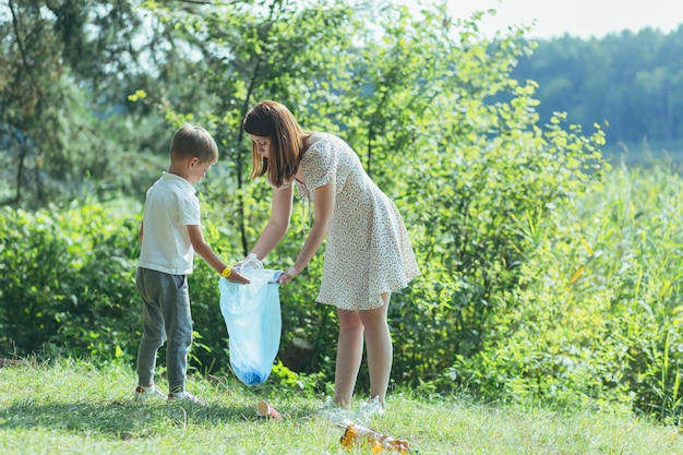 O voluntário da família limpa o lixo da natureza. pai e mãe, pais, filhos, filho família voluntários em um dia ensolarado limpando as garrafas de lixo na floresta de debri dobrando em saco plástico