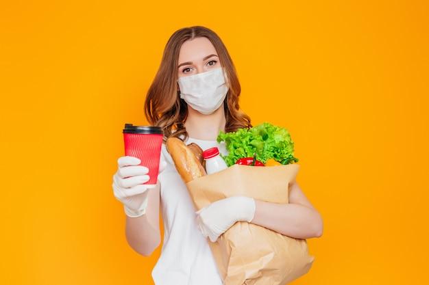 O voluntário de correio garota na máscara protetora detém um saco de papel com produtos, legumes, ervas, mostra uma xícara de café isolada sobre parede amarela, quarentena, coronavírus, entrega on-line de alimentos seguros