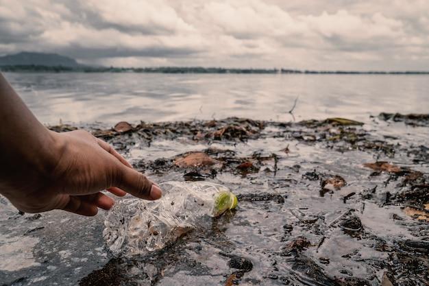 O voluntário pegar uma garrafa de plástico no rio