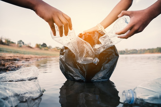 O voluntário que pega um plástico de garrafa no rio, protege o ambiente de um conceito de poluição.
