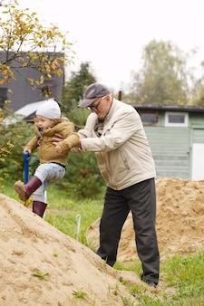 O vovô ajuda o neto a subir uma colina de areia