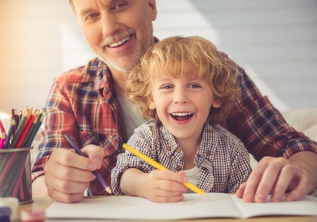O vovô e o neto consideráveis estão sorrindo.