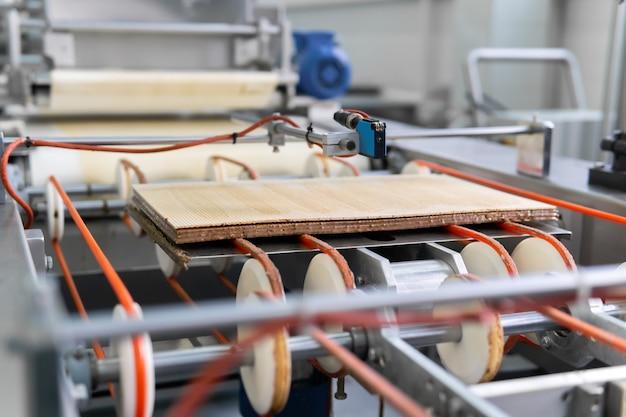 O wafer multicamada finalizado se move na esteira de uma fábrica de confeitaria