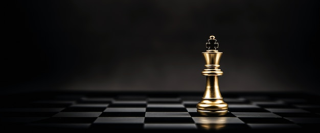 O xadrez do rei dourado está no tabuleiro de xadrez