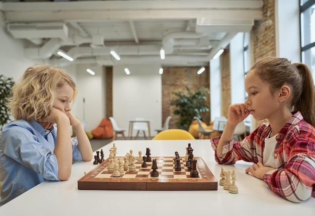 O xadrez é importante para crianças espertas, menino e menina, desenvolvendo estratégia de xadrez jogando jogo de tabuleiro sentado