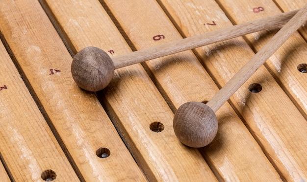 O xilofone close-up e duas marretas no fundo branco