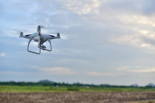 O zangão do avião descola da terra acima do campo para toma a foto aérea pela câmera no céu azul.