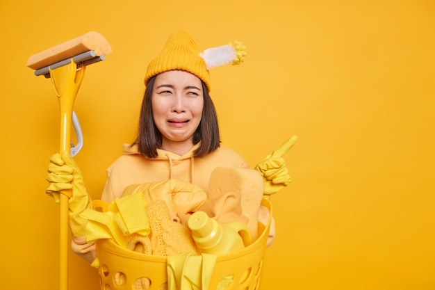 O zelador de mulher asiática chateado se sente triste e cansado usa esfregão para limpar poses de casa perto da bacia com roupa lavada vestida casualmente indica no canto superior direito isolado sobre fundo amarelo. limpeza de casa